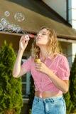 Burbujas de jabón de la muchacha que soplan rubia joven hermosa Fotos de archivo libres de regalías