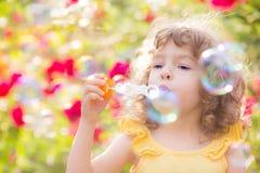 Burbujas de jabón del niño que soplan Foto de archivo libre de regalías