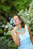 Burbujas de jabón jovenes de la muchacha que soplan hermosa y feliz al aire en fondo natural del parque verde en concepto del enc Imagenes de archivo