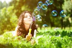 Burbujas de la mujer y de jabón en parque Chica joven hermosa que miente en el th Foto de archivo