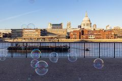 Burbujas de la sopa del ejecutante que soplan en día soleado hermoso en el banco del río Támesis Londres imagenes de archivo