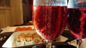 Burbujas de levantamiento del primer en vidrio con el champán rojo, tabla con el sushi, rollos en fondo almacen de metraje de vídeo