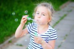 Burbujas de un jabón de la niña que soplan Fotos de archivo
