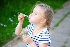 Burbujas de un jabón de la pequeña muchacha que soplan bonita Fotos de archivo