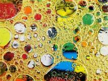 Burbujas del aceite de oliva en cierre del agua para arriba Foto de archivo libre de regalías