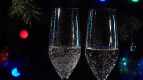 Burbujas del champán en vidrios en el fondo de un árbol de navidad Cámara lenta Cierre para arriba almacen de metraje de vídeo