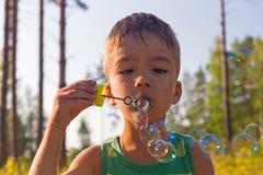 Burbujas del muchacho y de jabón Imágenes de archivo libres de regalías