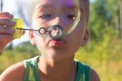Burbujas del muchacho y de jabón Imagen de archivo libre de regalías