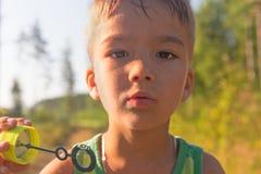 Burbujas del muchacho y de jabón Foto de archivo