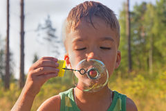Burbujas del muchacho y de jabón Foto de archivo libre de regalías