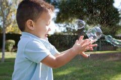Burbujas del niño y de jabón Foto de archivo libre de regalías