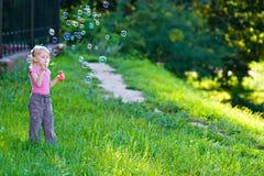 Burbujas del soplo de la muchacha Imagenes de archivo