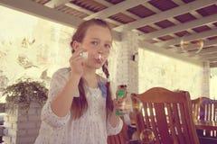 Burbujas del soplo de la muchacha Foto de archivo