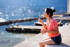 Burbujas del soplo de la muchacha en la playa Imagen de archivo libre de regalías