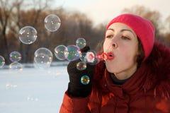 Burbujas del soplo de la muchacha en parque del invierno. Imagenes de archivo