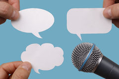 Burbujas en blanco del discurso con el micrófono Fotografía de archivo