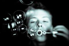 Burbujas en foco con el niño borroso en fondo Imagen de archivo