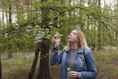 Burbujas hermosas de la muchacha y de jabón Fotografía de archivo
