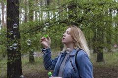 Burbujas hermosas de la muchacha y de jabón Imágenes de archivo libres de regalías