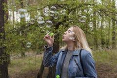 Burbujas hermosas de la muchacha y de jabón Fotografía de archivo libre de regalías