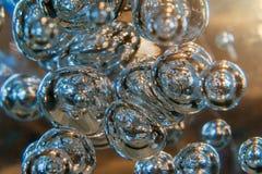 Burbujas iluminadas que flotan en el ambiente claro con el resplandor caliente de Sun Abstraiga la textura del fondo Viaje espaci imágenes de archivo libres de regalías