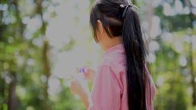 Burbujas juguetonas de la espuma de la muchacha linda feliz adorable en patio verde en verano al aire libre Niños en el parque co almacen de metraje de vídeo