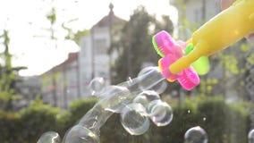 Burbujas que fluyen del arma del fabricante de burbuja en el área al aire libre urbana almacen de metraje de vídeo