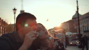 Burbujas que soplan abrazando el varón y a la pareja de matrimonios joven femenina metrajes