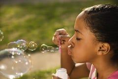Burbujas que soplan de la chica joven Imágenes de archivo libres de regalías