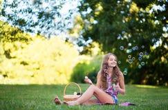 Burbujas que soplan de la chica joven Imagen de archivo