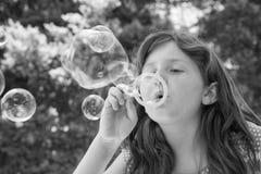 Burbujas que soplan de la chica joven fotografía de archivo