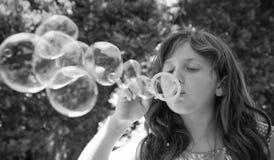 Burbujas que soplan de la chica joven foto de archivo