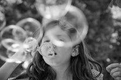 Burbujas que soplan de la chica joven fotografía de archivo libre de regalías