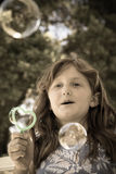 Burbujas que soplan de la chica joven fotos de archivo