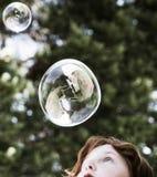 Burbujas que soplan de la chica joven foto de archivo libre de regalías