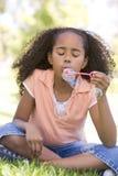 Burbujas que soplan de la chica joven al aire libre Imagenes de archivo