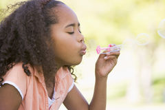 Burbujas que soplan de la chica joven al aire libre Foto de archivo libre de regalías