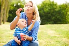 Burbujas que soplan de la madre para el muchacho joven en jardín Imagen de archivo