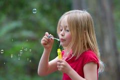 Burbujas que soplan de la muchacha. Imagen de archivo