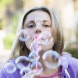 Burbujas que soplan de la muchacha adolescente Fotografía de archivo