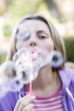 Burbujas que soplan de la muchacha adolescente Fotos de archivo