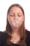 Burbujas que soplan de la muchacha adolescente en el fondo blanco Fotografía de archivo libre de regalías
