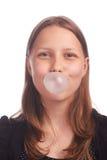 Burbujas que soplan de la muchacha adolescente en el fondo blanco Foto de archivo libre de regalías