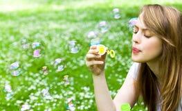 Burbujas que soplan de la muchacha al aire libre Foto de archivo