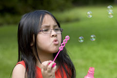 Burbujas que soplan de la muchacha con la varita Imágenes de archivo libres de regalías