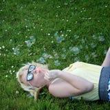 Burbujas que soplan de la muchacha en hierba Fotografía de archivo