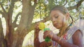 Burbujas que soplan de la muchacha en un parque almacen de video