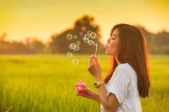 Burbujas que soplan de la muchacha hermosa joven Fotografía de archivo libre de regalías