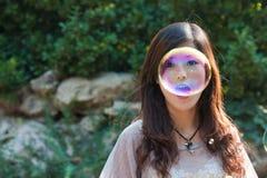 Burbujas que soplan de la muchacha hermosa joven en la naturaleza Foto de archivo
