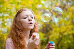 Burbujas que soplan de la muchacha joven del redhead Imágenes de archivo libres de regalías
